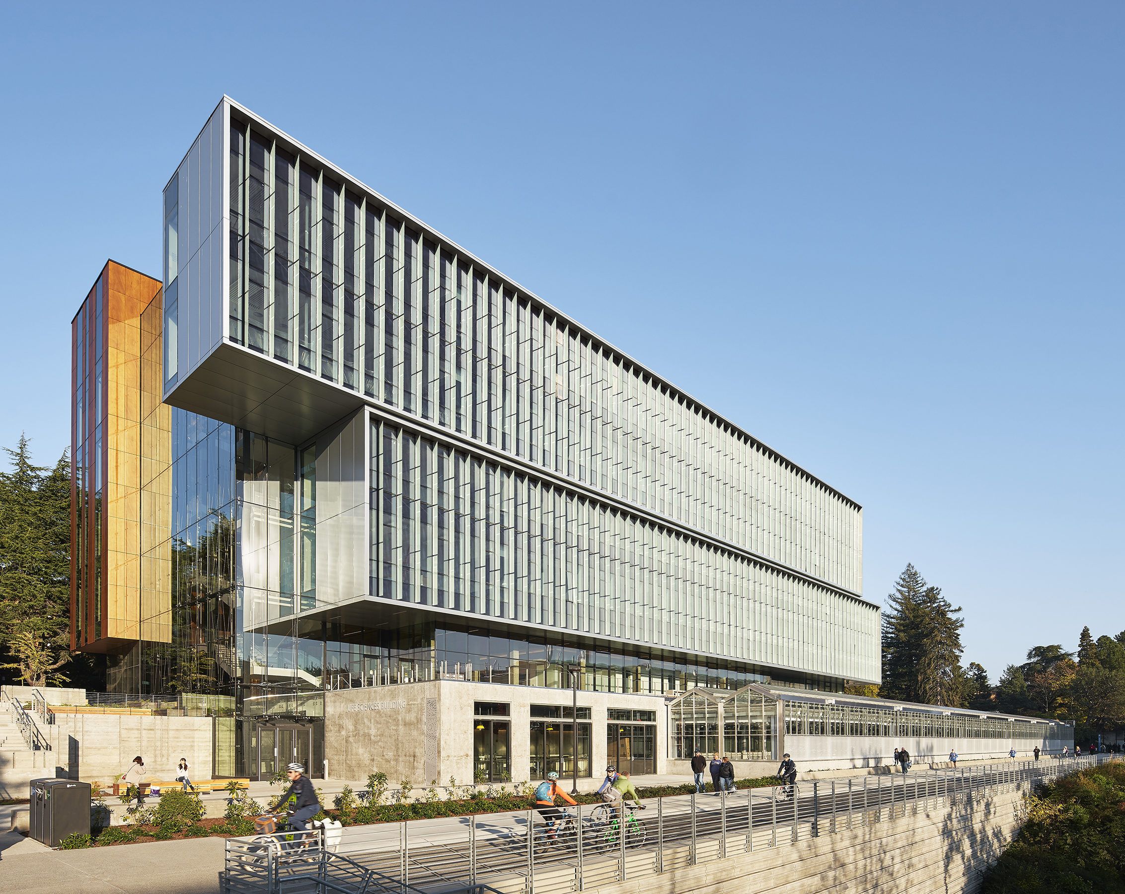 View of the south facade of UW Life Sciences Building with people biking and walking by on the Burke Gilman trail.