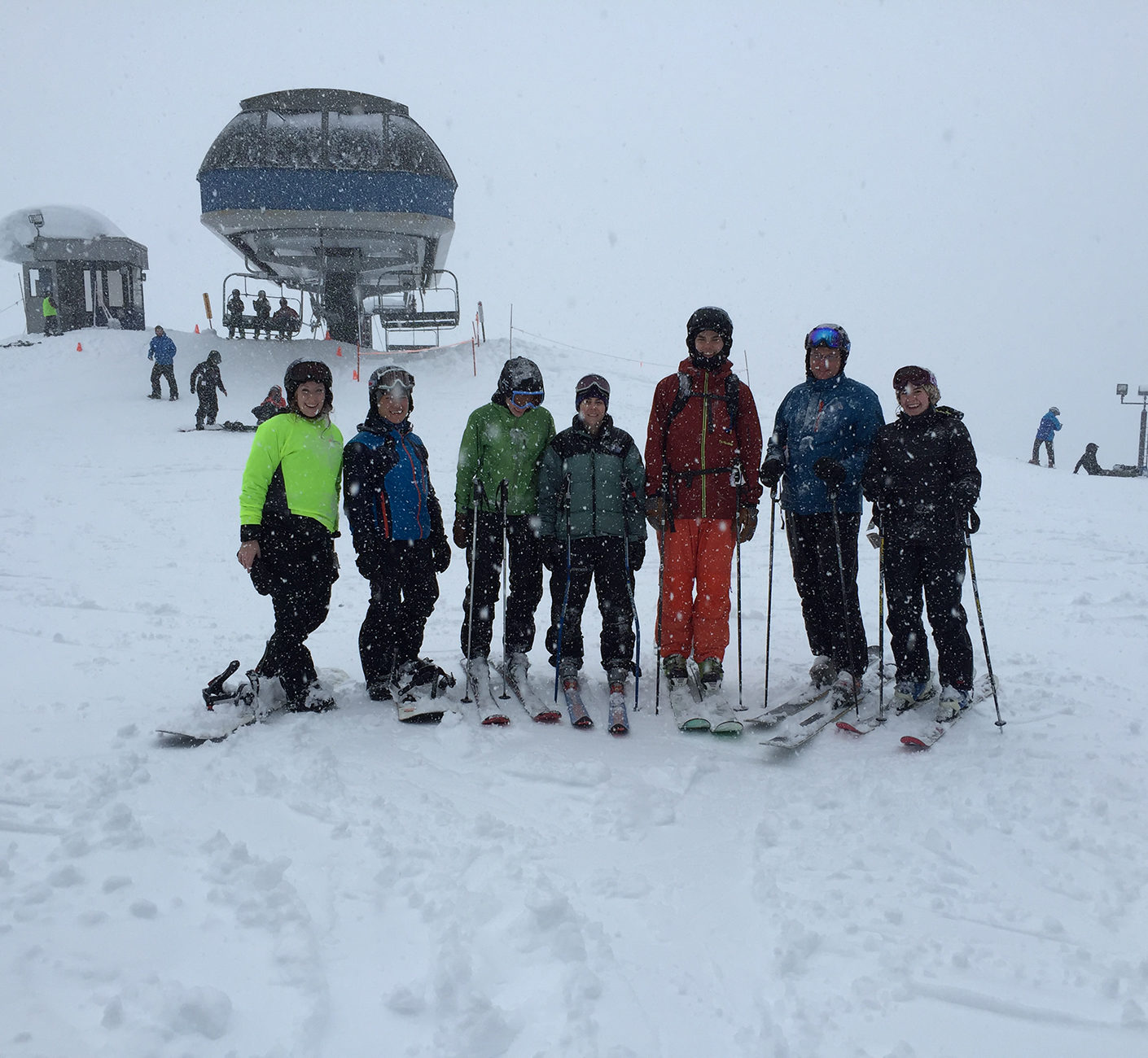 People on skis and snowboards on the top of a snowy mountain