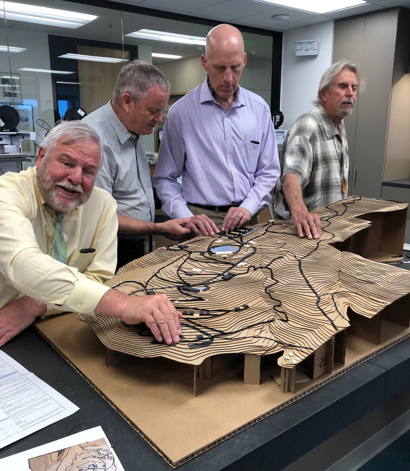 Demonstration of the tactile model. Four men feel the raised textures on the model.