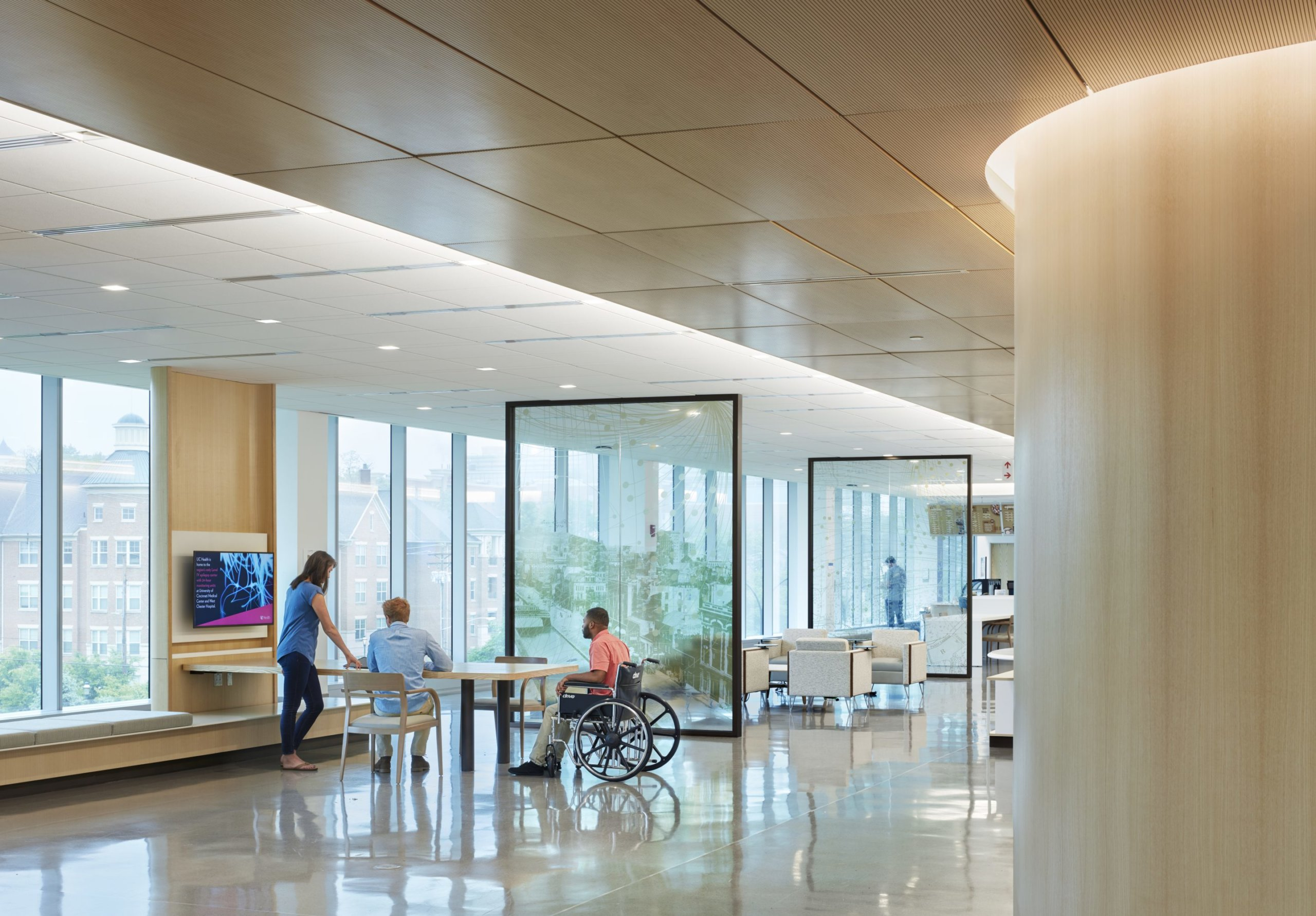 University of Cincinnati Gardner Neurological Institute. Main lobby that contains multi use areas for learning and waiting, museum, café, and classrooms. The spaces are divided by glass panels that contain artwork of the local culture of Cincinnati.